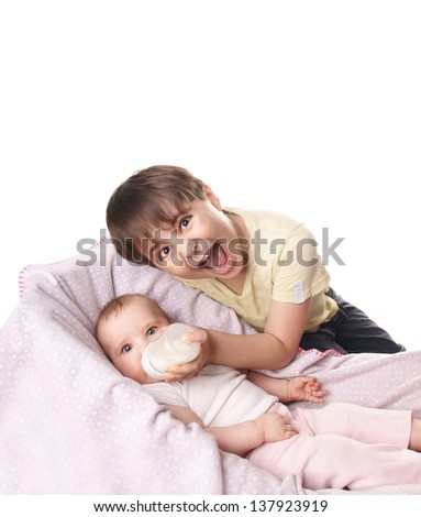 Older with crazy face brother feeding his little sister from bottle, isolated on white bakground - stock photo
