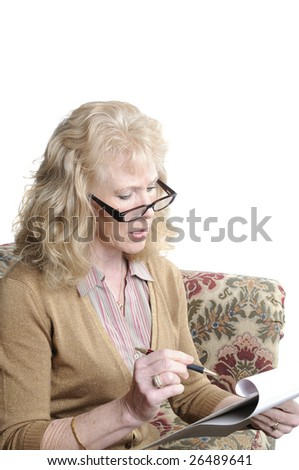 older woman going over her monthly expenses to determine what risk they have at losing her home during this economic crisis and the damage the stock market has had on her investments - stock photo