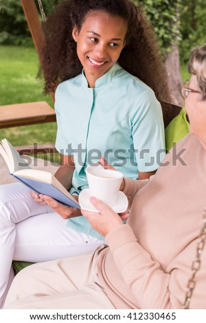 Older woman having afternoon tea in the garden - stock photo