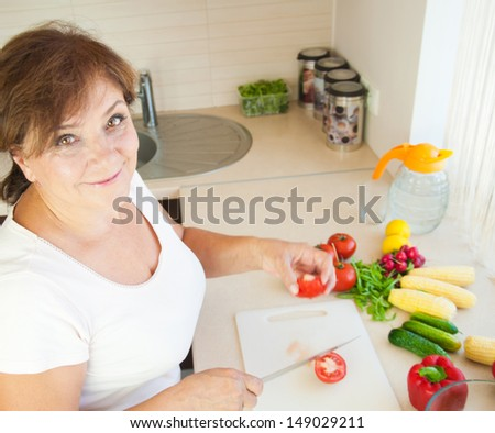 Older woman in kitchen preparing healthy food - stock photo