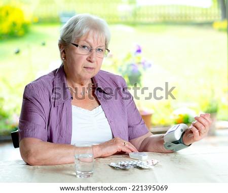 older woman is measuring blood pressure  - stock photo