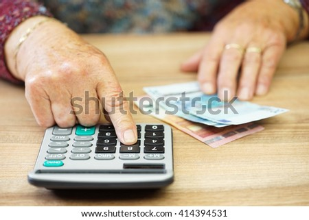 Older woman is using calculator to calculate all expenses - stock photo