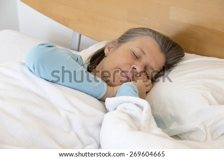 older woman lying in bed and sleeping peacefully - stock photo