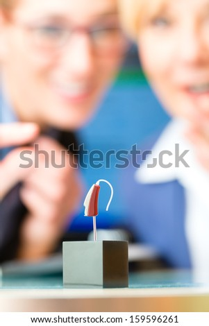 Older woman or female pensioner with hearing problem make a hearing test, in the foreground is a model of a hearing aid - stock photo