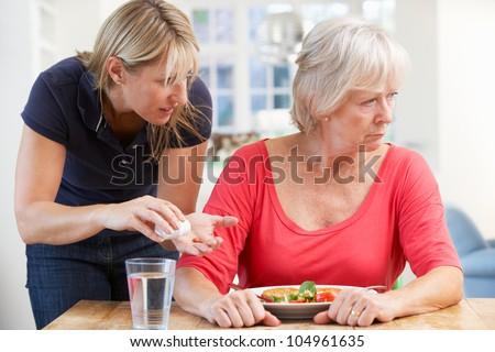 Older woman refusing medication at home - stock photo