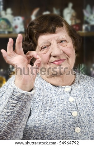 Older woman 80s  showing okay hand sign and smiling for you - stock photo