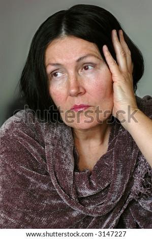 Older woman, sitting alone and looking away into the distance - stock photo