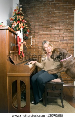 Older woman sitting at an upright piano at Christmas time getting ready to play while the family dog looks on curiously - stock photo