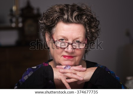 Older woman smiling in her living room. Smiling friendly senior woman sitting on a chair in her living room. Elderly woman. Close up. - stock photo