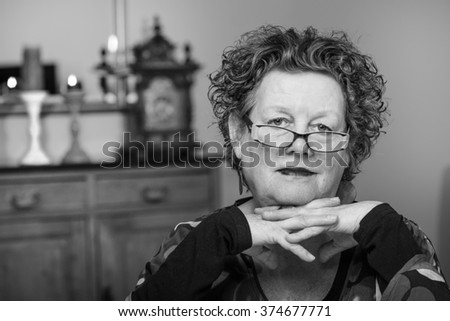 Older woman smiling in her living room. Smiling friendly senior woman sitting on a chair in her living room. Elderly woman. Black and white. - stock photo