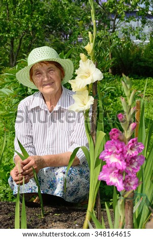 Older woman smiling on a bed with white and purple gladioli.