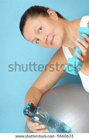 Older woman staying fit with dumbbells and an exercise ball - stock photo