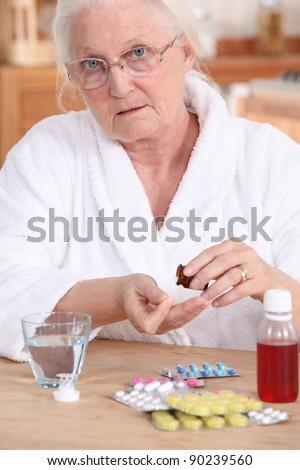 Older woman taking medicine - stock photo