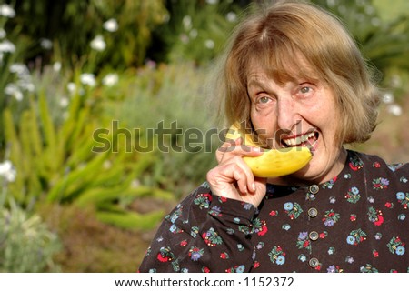 Older woman talks into banana instead of phone - stock photo