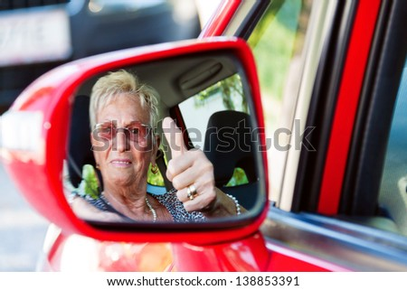 older woman wearing a seatbelt when in a car. - stock photo