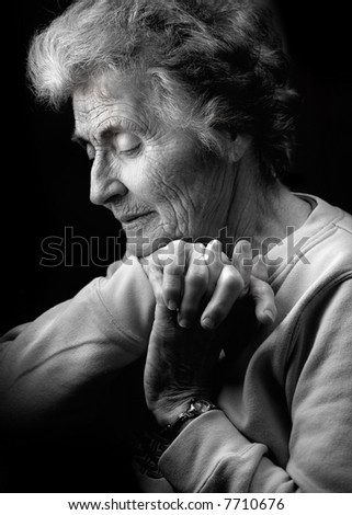 Older woman with head bowed.