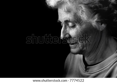 Older woman with head bowed in thought