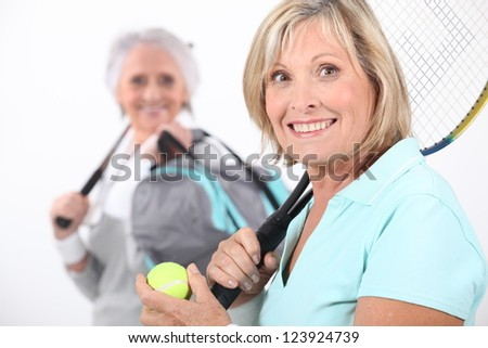 Older women playing tennis - stock photo