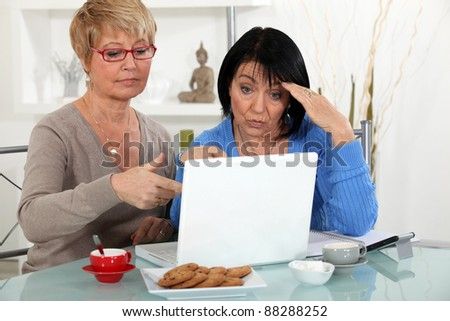 Older women puzzling over a laptop - stock photo