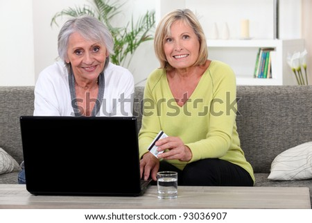 Older women using a credit card online - stock photo