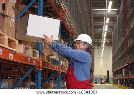older worker in uniform moving,taking out,putting,segregating,lifting on (from) shelves in warehouse - stock photo
