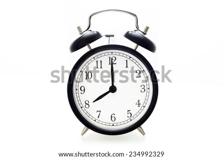 Oldfashioned black glossy alarm clock showing 8 o'clock