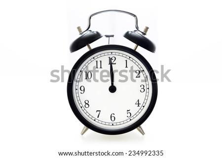 Oldfashioned black glossy alarm clock showing 12 o'clock - stock photo