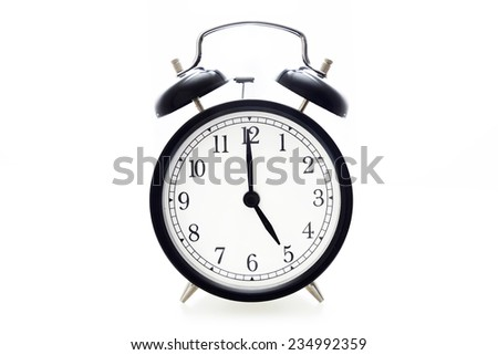 Oldfashioned black glossy alarm clock showing 5 o'clock - stock photo