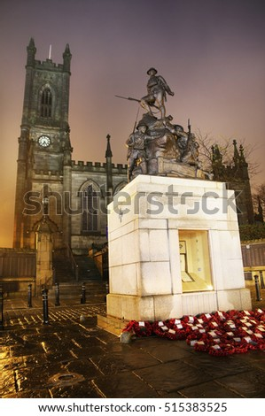 OLDHAM, UK - NOVEMBER 14, 2016: Cenotaph and Oldham Parish Church. Oldham is a town in Greater Manchester and rose to prominence in the 19th century as an international centre of textile manufacture