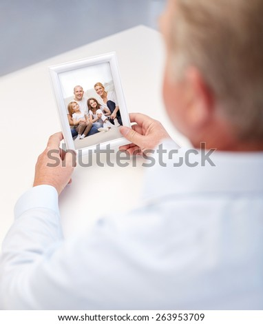 oldness, memories, nostalgia and people concept - close up of old man holding and looking at happy family photo - stock photo