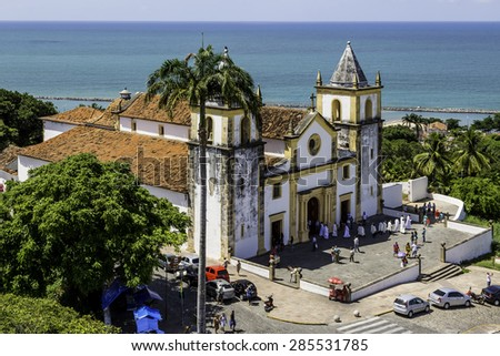 OLINDA, BRAZIL - MAY 1: Aerial view of Olinda in PE, Brazil showcasing its historic architecture with the Baroque Se Church after a service with priests and locals passing by on May 1, 2015 in Olinda. - stock photo