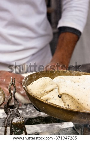 Olive bread dough on a baker balance in a craftsman market.Vertical image.