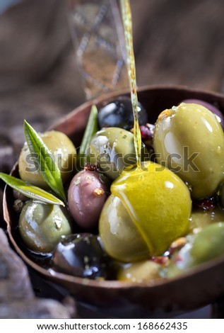 Olive fruit and leaves soaked in olive oil.  - stock photo