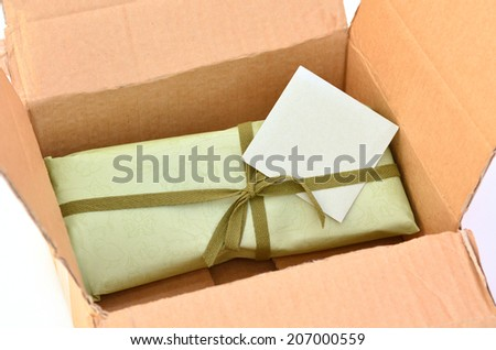 Olive green gift box with dark green ribbon and bow with gift card inside a cardboard delivery box.Concept photo of birthday, holidays, life events, wedding and special occasion - stock photo