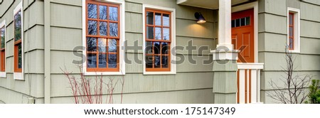 Olive house with orange color front door and windows. - stock photo