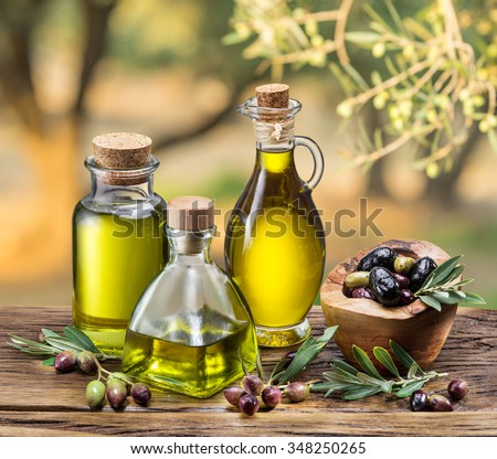 Olive oil and berries are on the wooden table under the olive tree.  - stock photo