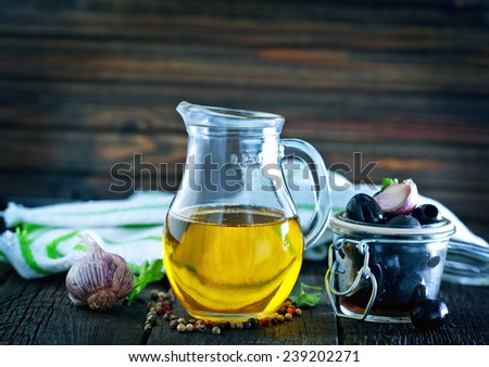 olive oil and black olives on the wooden table - stock photo