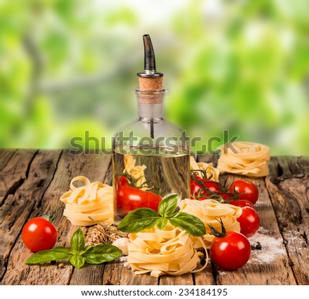 Olive oil and different types of pasta on wooden table with nature green background
