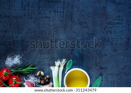 Olive oil and fresh cooking ingredients (young green onions, peppercorns, tomatoes, garlic, rosemary) on dark vintage background. Organic vegetables. Cooking, Healthy Eating or Vegetarian concept. - stock photo