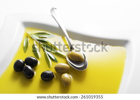 Olive oil and green olive branch in bowl - stock photo