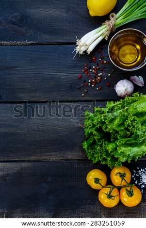 Olive oil and ingredients for cooking on dark wooden background - healthy or vegetarian eating concept. Space for text, top view. - stock photo