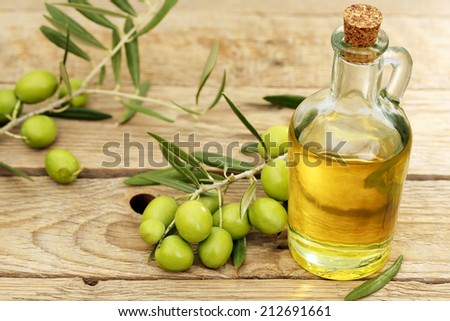 olive oil and olive tree branch on wood - stock photo