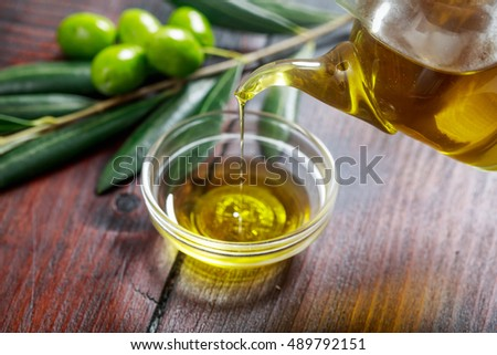 Olive oil and olive twig on a table