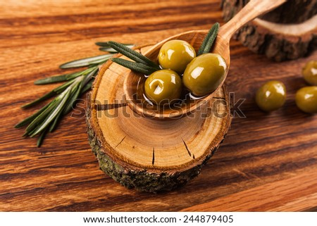 Olive oil and olives in wooden spoon with rosemary, lying on the wooden table - stock photo