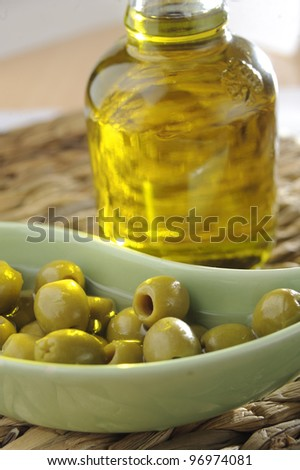 Olive oil and olives on a beige background - stock photo