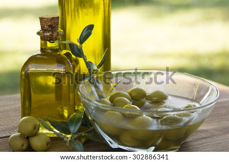 olive oil and olives on wooden background