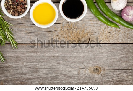 Olive oil and vinegar with spices over wooden table background with copy space - stock photo