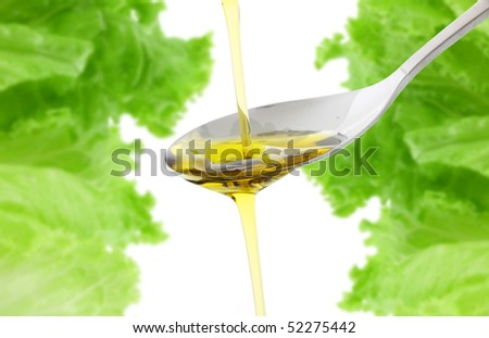 olive oil being poured into a spoon - stock photo