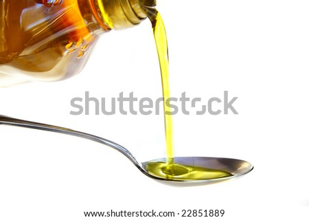 olive oil being poured into a spoon, isolated on white