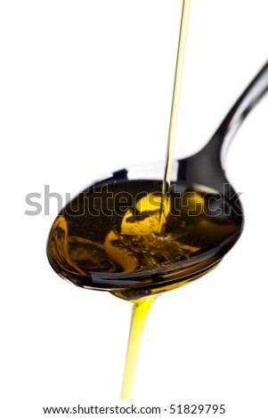 olive oil being poured over a spoon